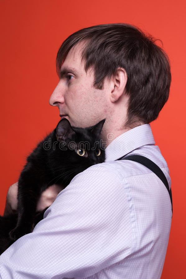 Side view of serious handsome man with dark hair in shirt holding near chest cute black cat. And looking away on orange background with copy space royalty free stock image