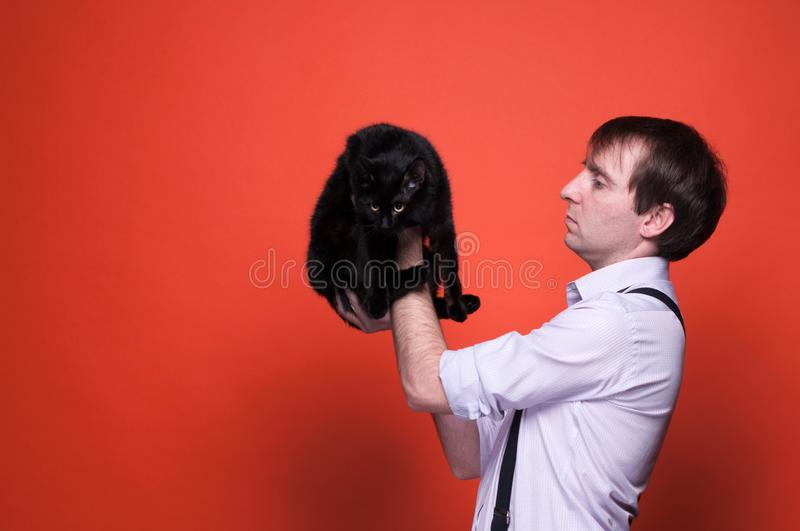 Erious handsome man in shirt with rolled up sleeves holding on outstretched arms cute black cat smiling and looking at it. Side view of serious handsome man in royalty free stock photos