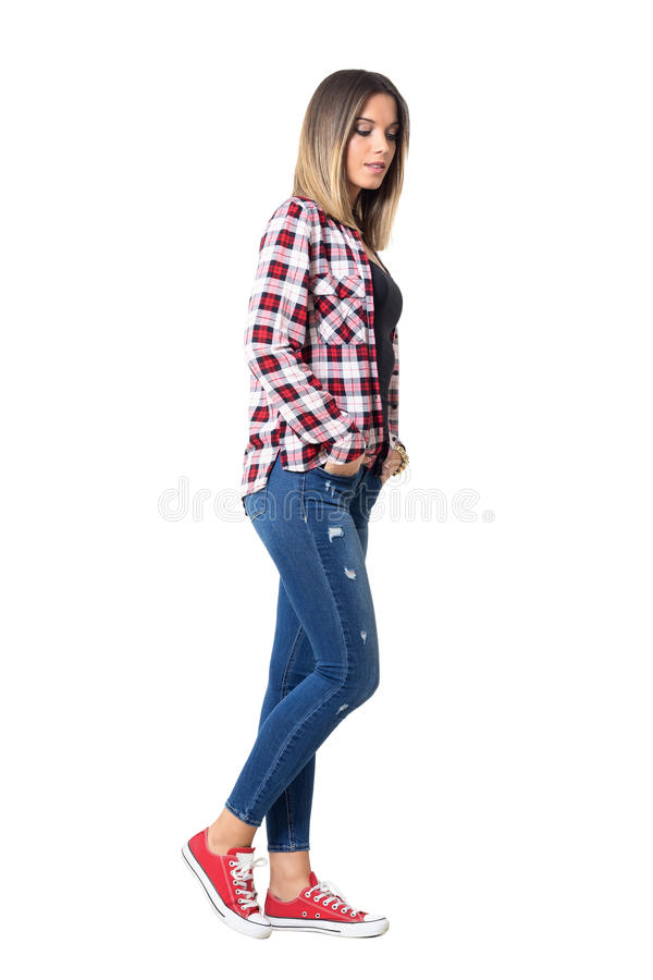 Side view of serious young beautiful girl with hands in pockets walking and looking down. stock photo