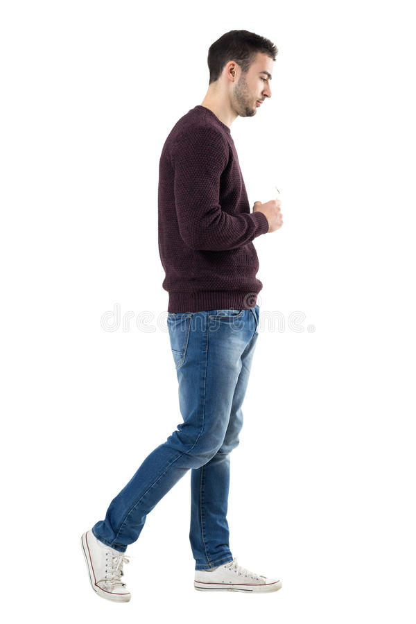 Side view of serious young man holding sunglasses walking and looking down stock photo