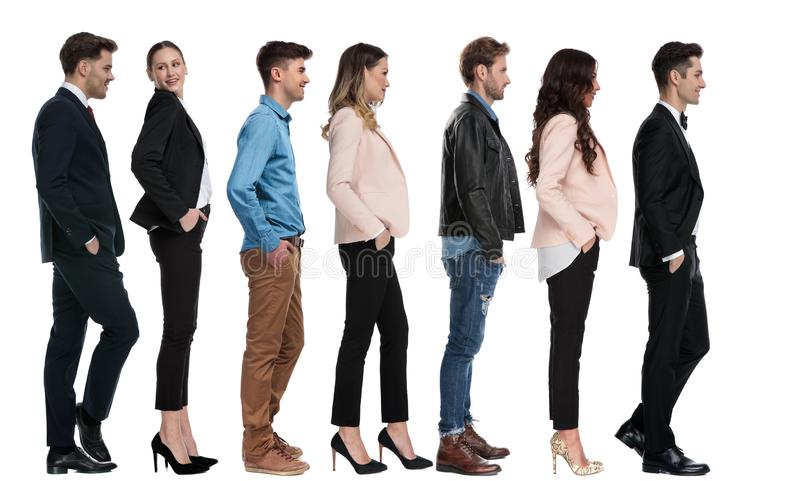 Side view of seven different people waiting in line royalty free stock photos