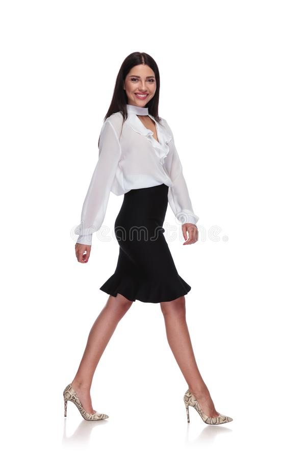Side view of businesswoman in black skirt stepping stock photo