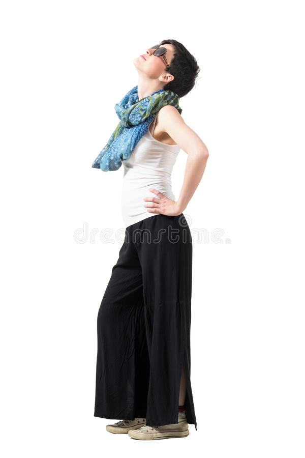 Side view of short hair woman wearing sunglasses with hands on hips looking up stock images