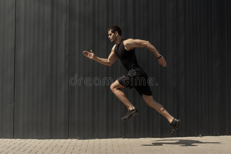 A side view shot of a fit young, athletic man jumping and runnin royalty free stock photos