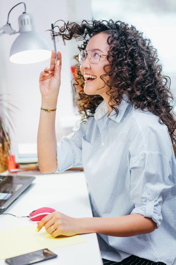Side view shot of laughing young female playing with her curly hair at the table royalty free stock photo