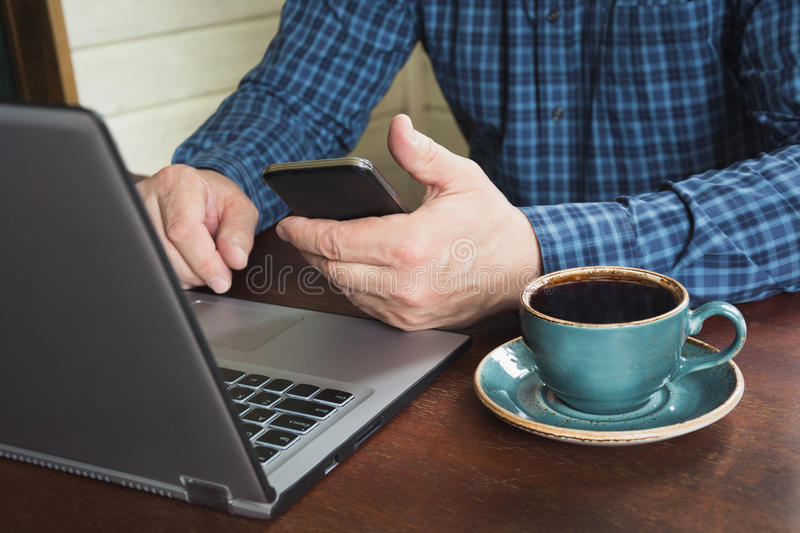 Side view shot of a man`s hands using smart phone and laptop sitting at wooden table with cup of black coffee. Close up. royalty free stock photography