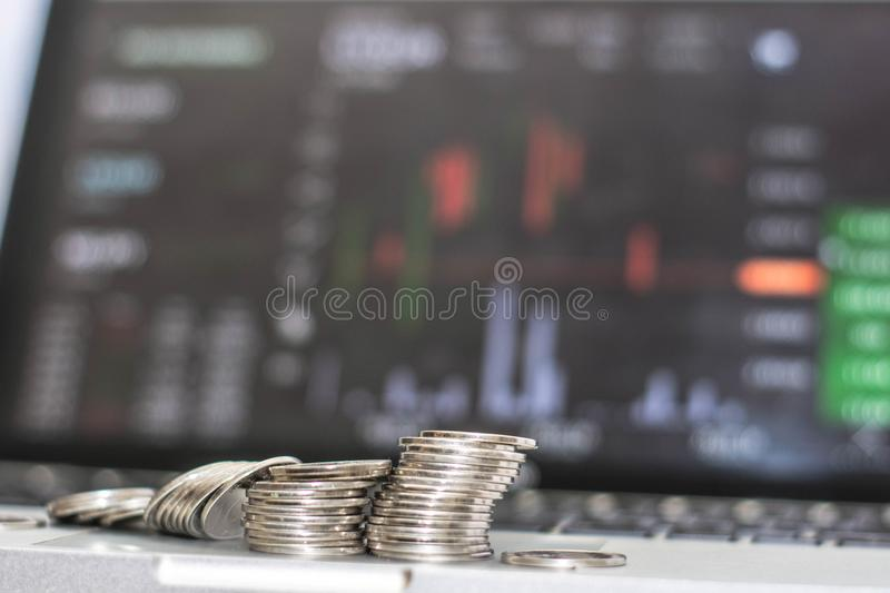 Side view of silver coin with monitor shows trading traffic, Bitcoin minning. Shiny silver coin colapse infront of monitor computer and laptop screen royalty free stock photos