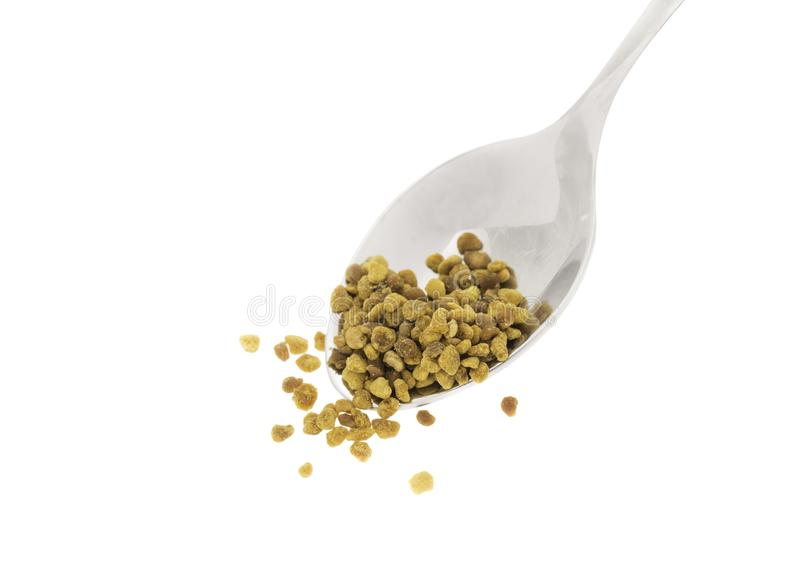Side view of silver spoon with bee pollen, white background royalty free stock image