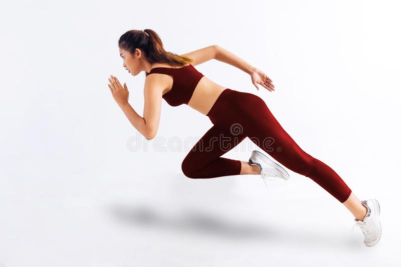 Side view of slim Asian female in red sportswear sprinting fast against white background royalty free stock photography