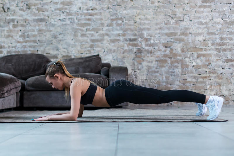 Side view of slim female athlete standing in plank position on floor strengthening core muscles indoors royalty free stock images