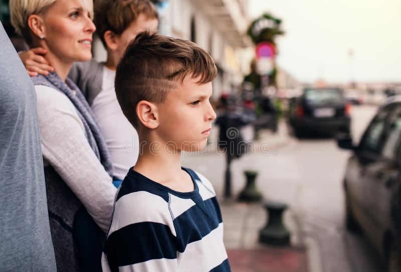 Side view of small boy with family standing outdoors in town. royalty free stock images