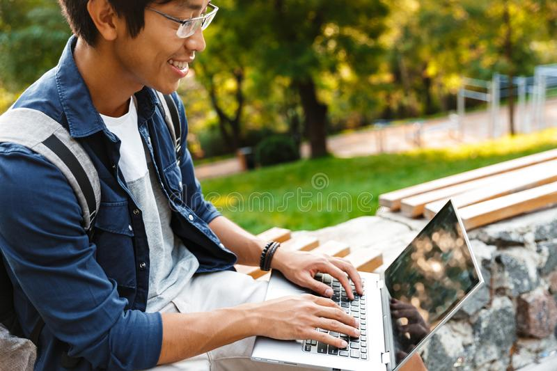 Side view of Smiling asian male student in eyeglasses. Using laptop computer while sitting on bench in park stock photo