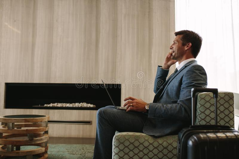 Business traveler waiting for his flight in airport lounge stock photography