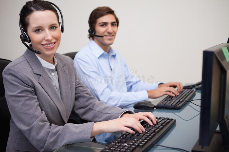 Side view of smiling call center agents at work royalty free stock image