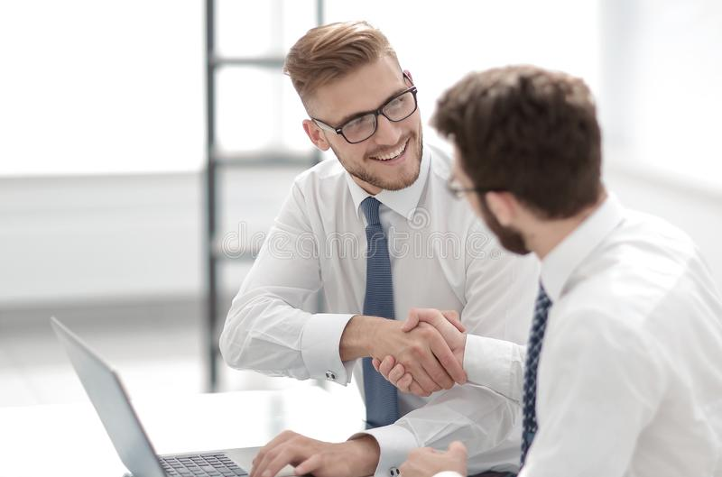 Side view.smiling employees shaking hands stock photos