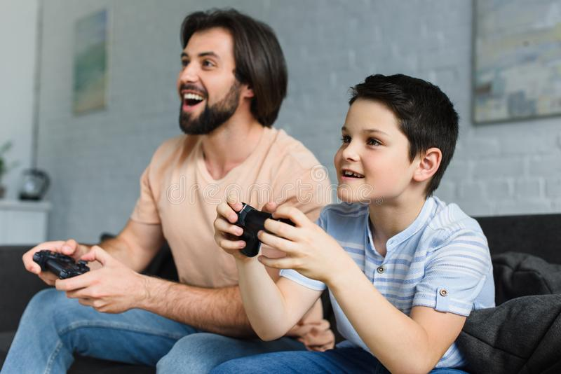 Side view of smiling father and son playing video games together. At home stock photography