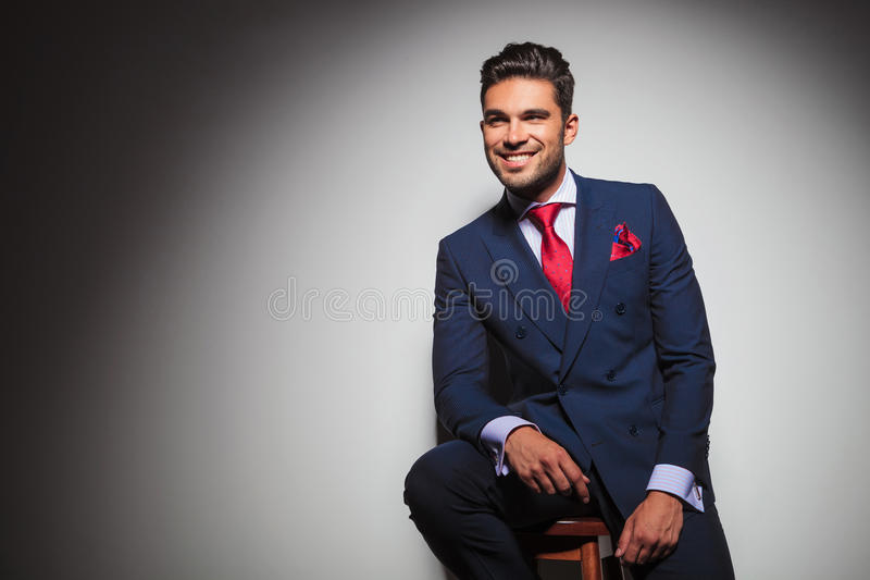 Side view of a smiling gentleman sitting on a chair stock photos