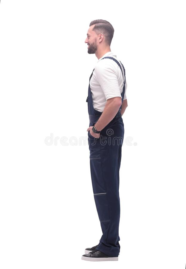 Side view. smiling man in blue overalls. isolated on white royalty free stock images