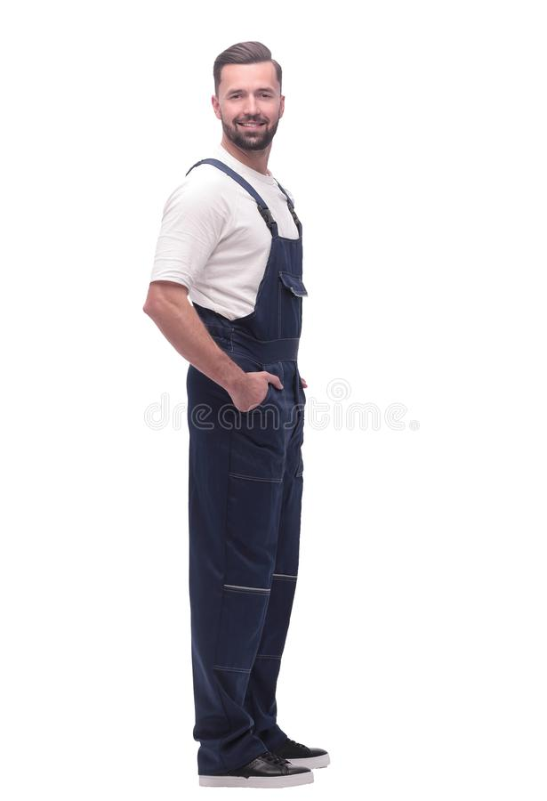 Side view. smiling man in overalls looking forward to copy space royalty free stock image