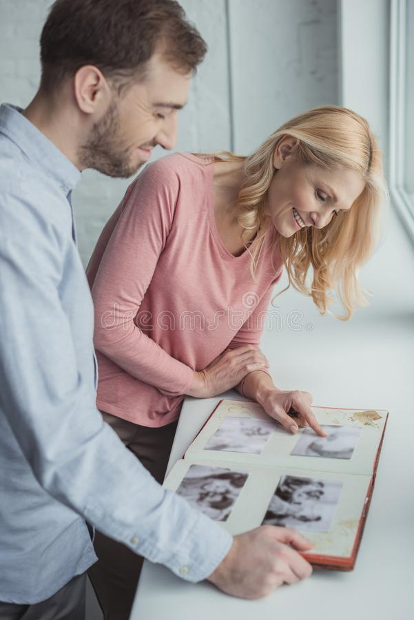 side view of smiling mother and grown son looking at photo album together royalty free stock image