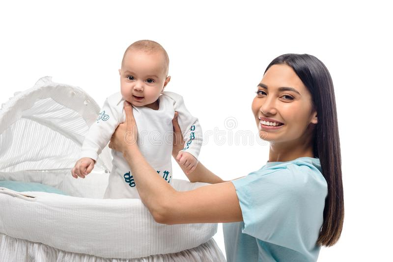 Side view of smiling mother taking baby out of crib. Isolated on white stock photo
