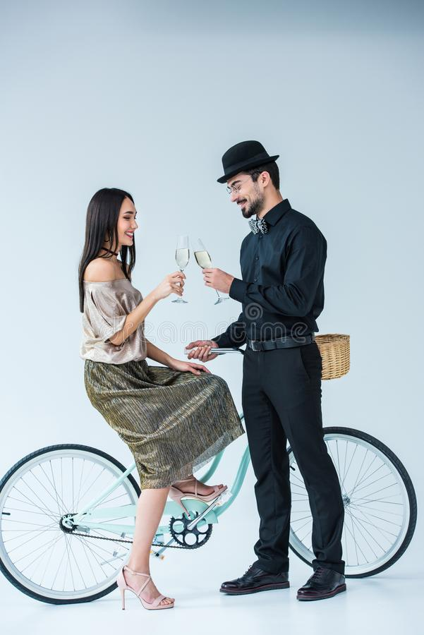 side view of smiling multicultural couple with retro bicycle clinking glasses of champagne stock image