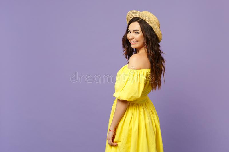 Side view of smiling pretty young woman in yellow dress, summer hat looking camera  on pastel violet wall stock images