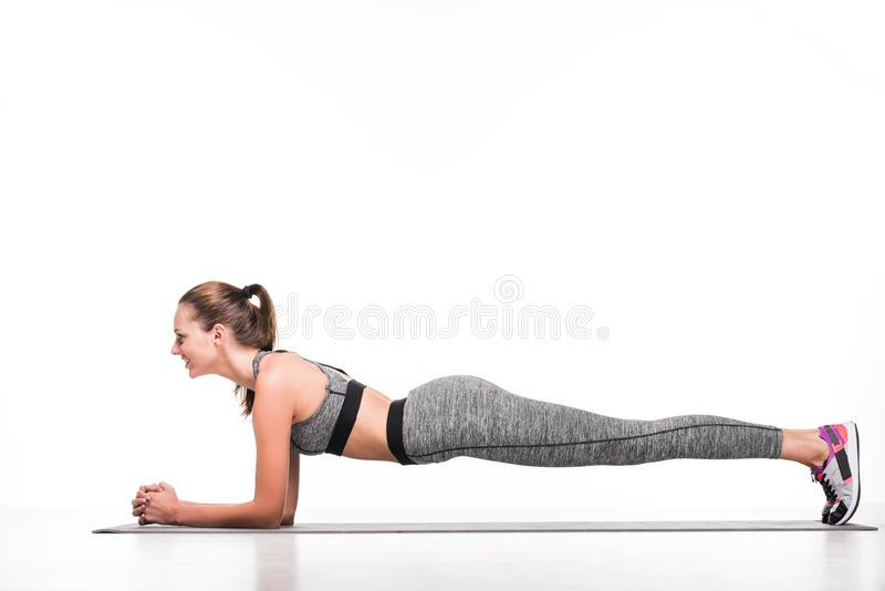 side view of smiling sportswoman doing plank exercise on yoga mat stock photo