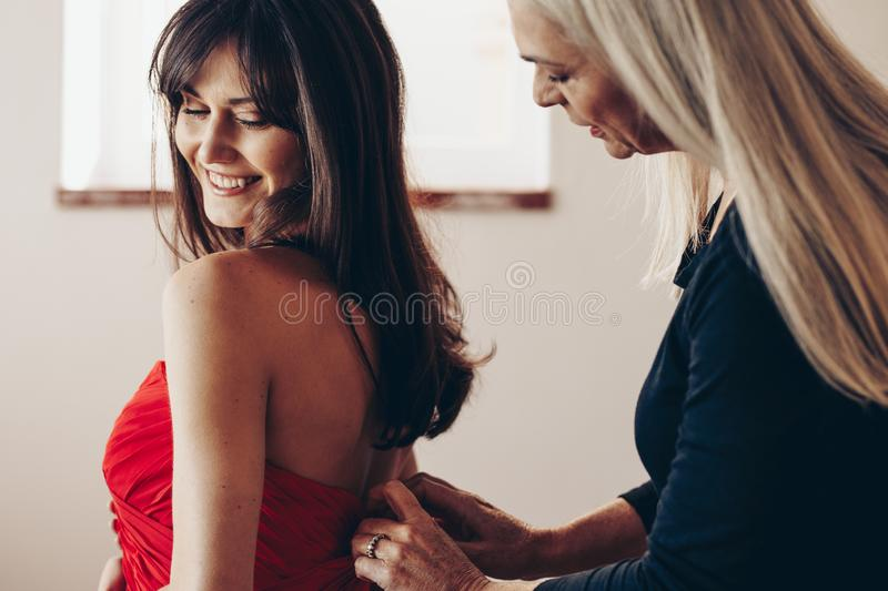 Side view of a smiling woman being helped by her mother. Elderly woman putting hooks on the dress of a young lady. E view of a smiling women being helped by her royalty free stock images