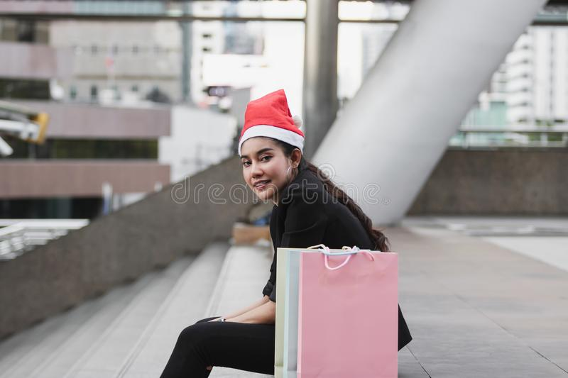 Side view of smiling young Asian woman with santa hat and colorful shopping bag sitting outdoors after shopping for christmas gift royalty free stock photos