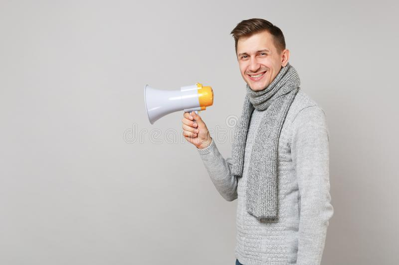 Side view of smiling young man in gray sweater scarf holding megaphone on grey background in studio. Healthy stock image