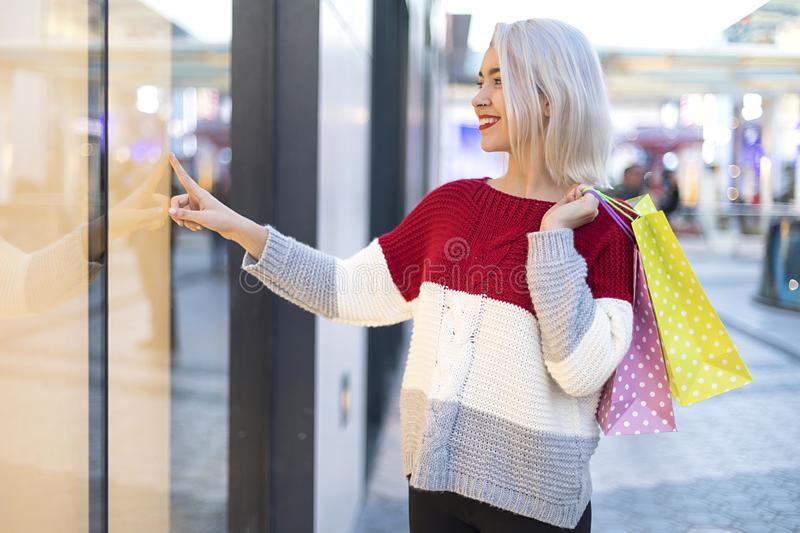 Side view of a smiling young woman standing in a shopping center while looking to window mall royalty free stock images
