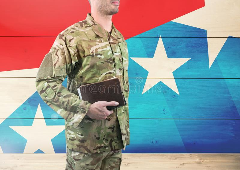 Side view of soldier holding a book in front of american flag royalty free stock image