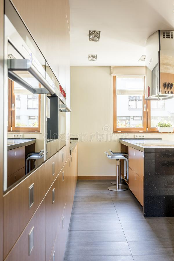 Side view of spacious kitchen. With bar chairs under the window royalty free stock images