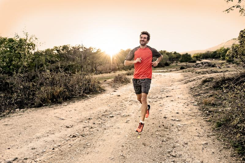 Sport man with ripped athletic and muscular legs running downhill off road in jogging training workout royalty free stock photos