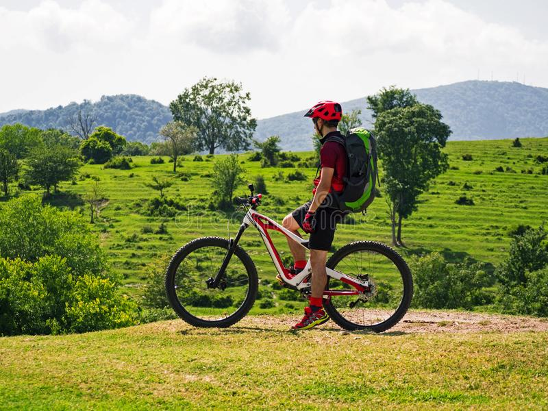 Sports man on mountain bike at alpine fields background stock images