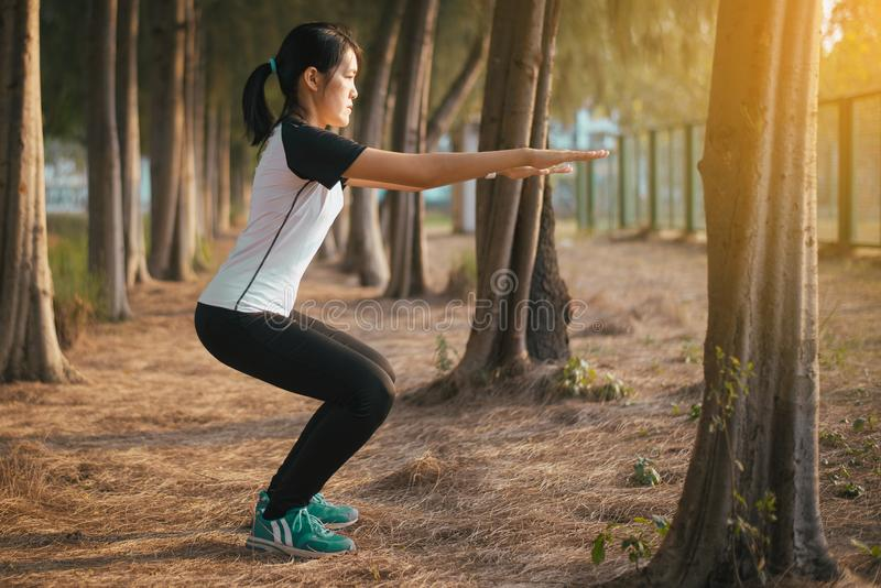 Side view of sporty athletic asian woman doing squatting,Beautiful female slim lady model practice balance and focused strong leg stock image