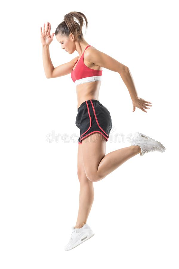 Side view of sporty focused confident fitness woman jumping movement. stock photo