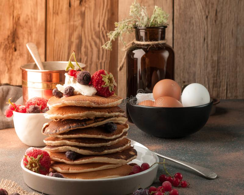 Stack of delicious brown traditional american pancakes with sour cream and fresh berries royalty free stock photography