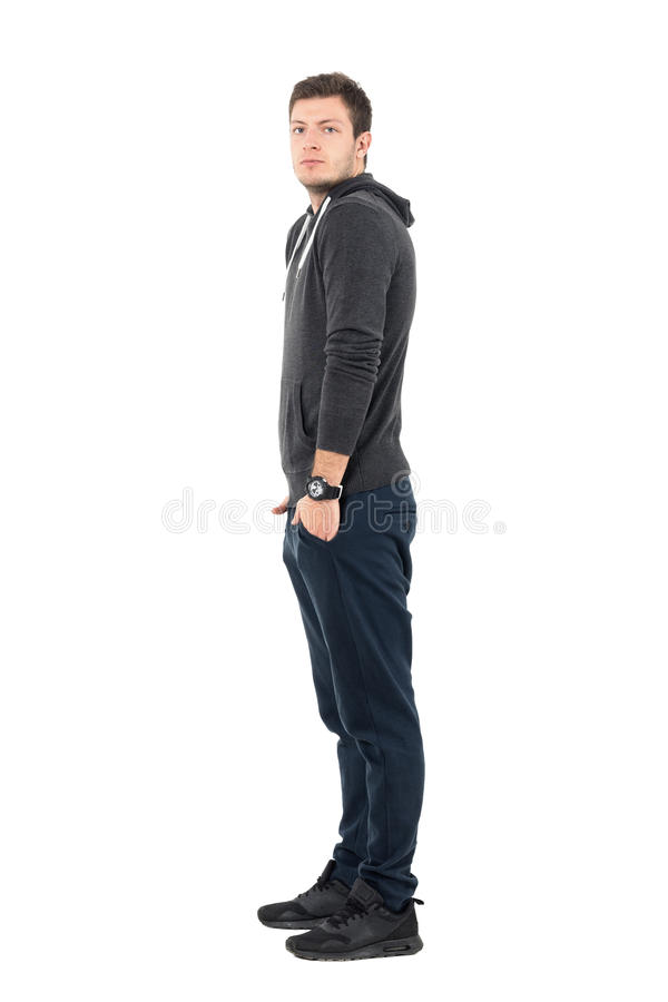 Side view of standing young man in sportswear with hands in pockets looking at camera stock photography