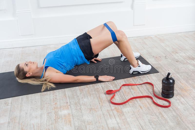 Side view of strong and fit athletic young caucasian woman in sportwear with bands training legs and glutes muscular. Fitness exercising with expander. Indoor royalty free stock photography
