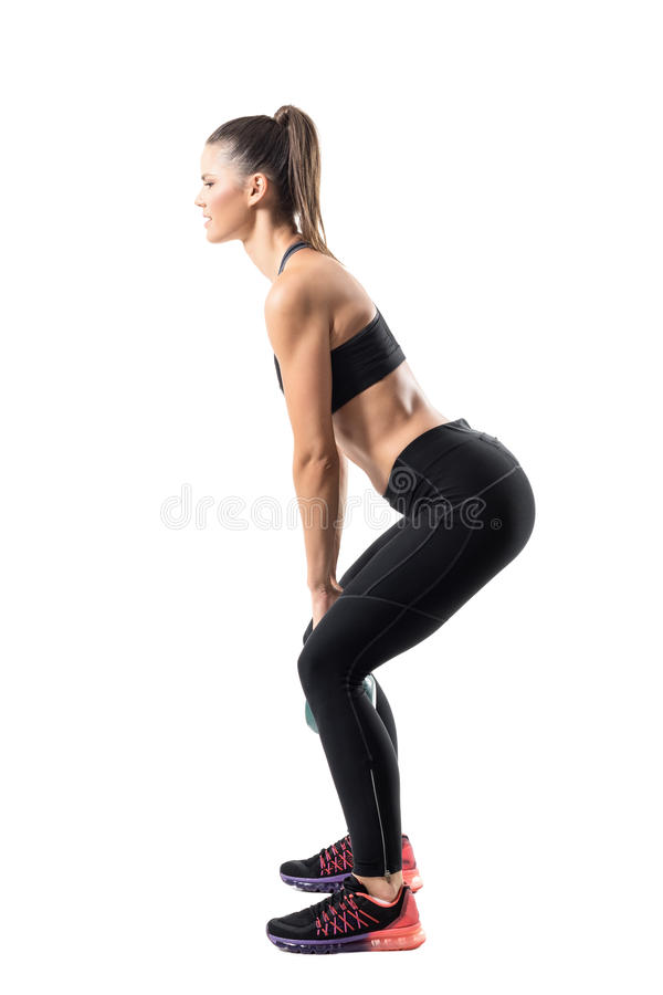 Side view of strong fitness gym girl swinging kettlebell in lower position. royalty free stock image