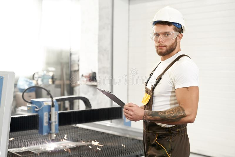 Side view of strong mechanic in protective glassesn working. Side view of strong mechanic in protective glasses, helmet and uniform looking at camera and posing stock photography