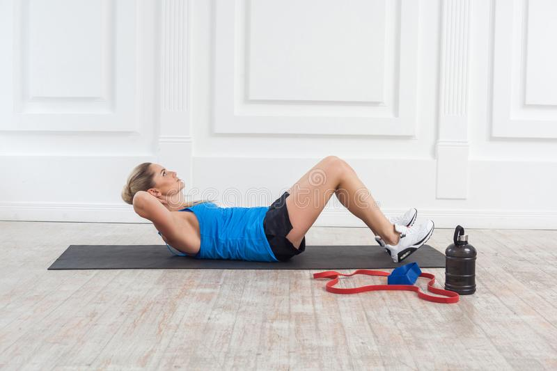 Side view of strong sporty beautiful young athletic blonde woman in black shorts and blue top working in gym doing exersice for. Perfect press. Indoor, studio stock image