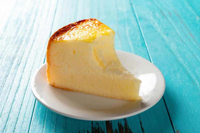 Side view studio shoot of a home made cheese cake on a blue table. Side view studio shoot of home made cheese cake on a blue table with a bite stock photo