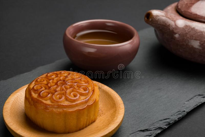 Side view studio shoot of traditional Chinese mooncake with tea and teapot on black. Background stock images