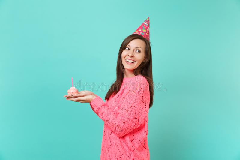 Side view of stunning young woman in knitted pink sweater birthday hat looking back, holding cake with candle isolated royalty free stock photography
