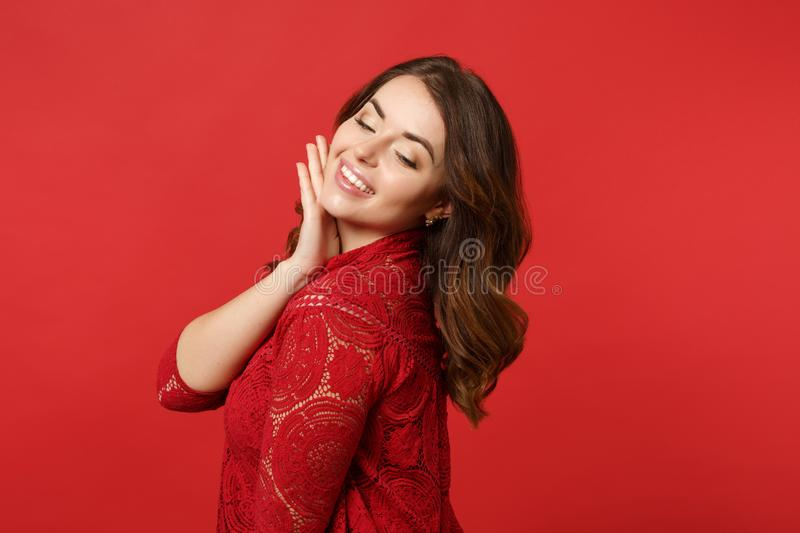 Side view of stunning young woman in lace dress put hand prop up on chin, looking down isolated on bright red wall stock photography