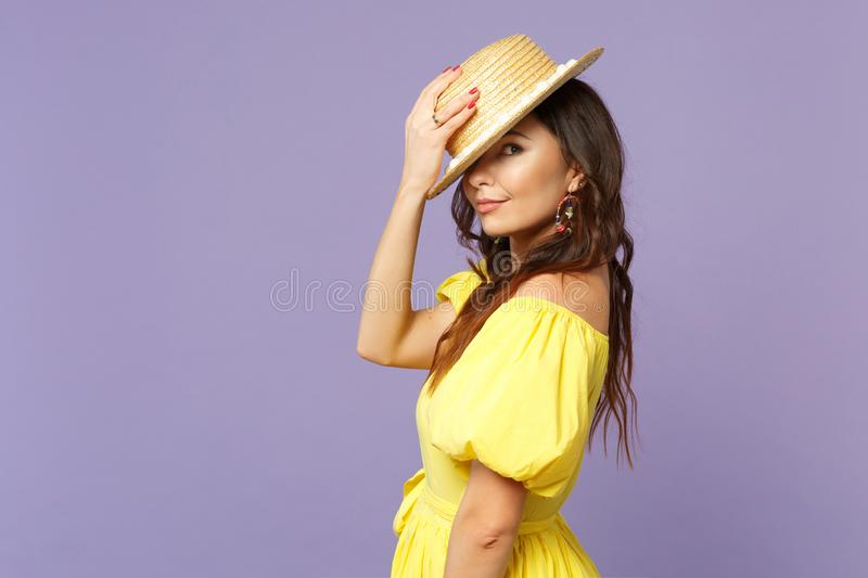Side view of stunning young woman in yellow dress holding summer hat on head, looking camera isolated on pastel violet. Wall background. People sincere emotions stock image