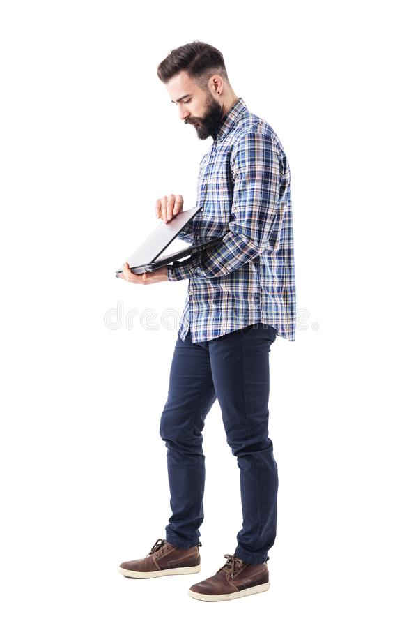 Side view of stylish bearded modern business man opening laptop computer. stock images